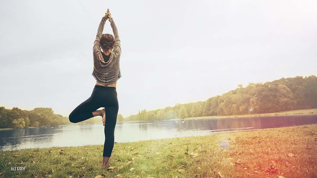 Woman holding a Vrksasana yoga pose in autmny park